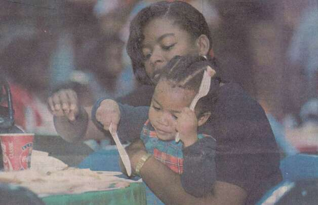 """Carol Nash of Beaumont holds her 2-year-old son, Jamard, in her lap as they eat Friday afternoon during the 'Feast of Sharing' at the Civic Center."" File photo Dec. 24, 1994"