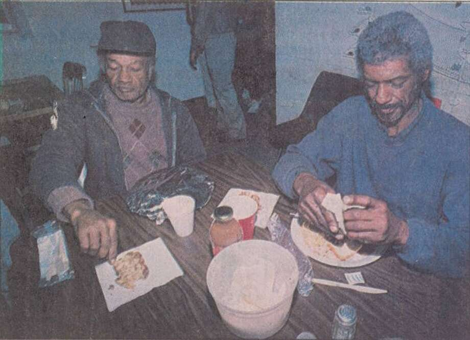"""David Spikes, left, and Allen Phillips enjoy Christmas dinner Sunday at the Salvation Army headquarters on Sabine Pass Avenue."" File photo Dec. 26, 1994"