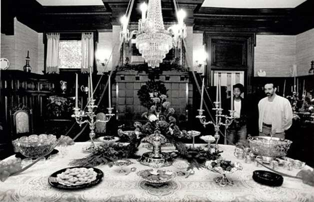 "BEAUMONT - ""At right, standing l-r: Tracye Thomas and Sam Daleo, Jr. feast their eyes on the festive dining room which is decorated for Christmas inside the McFaddin Ward House."" Beaumont Enterprise, 1992"
