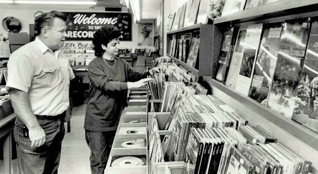 """Jimmy Conn and Carol Young of the Record Rack look through the store's selection of Christmas music."" File photo Nov. 26, 1991"