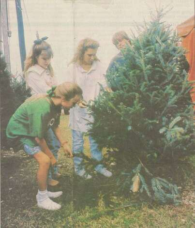 """The Kirk family shops for the Perfect Christmas tree at a local nursery. Holli Kirk, front, Britini Kirk, center, and Traci Kirk inspect a tree held by Brady Phillips."" File photo Dec. 2, 1991"