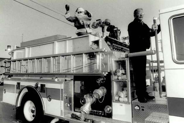 """Santa rides atop a Nederland firetruck at the end of the parade throwing candy to the kids."" File photo Dec. 3, 1991"