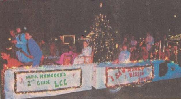 """Second-graders from Little Cypress Elementary School 'saw Mommy kissin' Santa' on their float Friday night as it moved along with dozens of other floats and bands in the 42nd annual Jaycees Parade in Orange."" File photo Dec. 11, 1991"