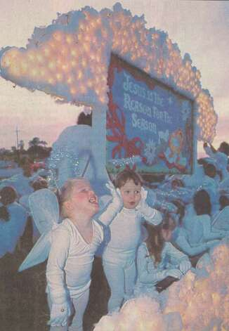 """Orange residents Kaitlin McWilliams, 3, and Jeana Teague, 4, delight in the onset of the Orange Jaycees Parade Friday night as the floats line up in the MacArthur Shopping Center parking lot."" File photo Dec. 11, 1991"