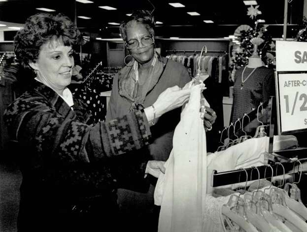 """Charlotte Eddleman, of Winnie, made the trip into Beaumont in spite of inclement weather to check out post-Christmas sales like the one at White House in Gateway Shopping Center. Charlie Twine, of Beaumont, a fourteen-year employee of the White House, shows Eddlemen ready to wear women's apparel."" File photo Dec. 26, 1991"