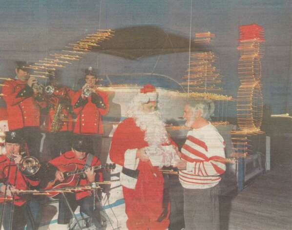 """Part of the Beaumont Fire Department Band performs as Santa (Fire Chief Pete Shelton) greets Ross Bennett on the dock at Riverfront Park. The band members are, clockwise from lower left, Tommy May, Jerry May, Derwin Daniels, David May and Charles Glen."" File photo Dec. 15, 1989"