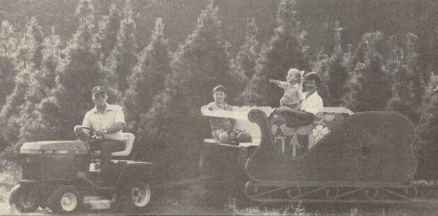 """Preston Nichols takes Christopher Nichols, Carly Standley and Donna Nichols on a 'sleigh' ride through the farm."" File photo Nov. 25, 1988"