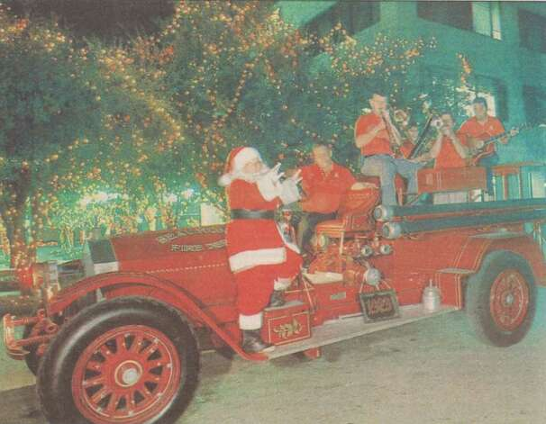 """The Beaumont Fire Department Band performs atop a truck while Santa listens."" File photo Dec. 9, 1988"