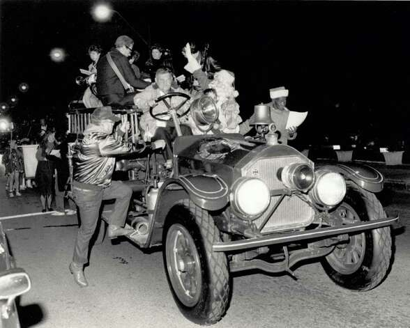 """With a wave of his hand, Santa Claus signals the beginning of the fourth annual Holiday Fantasy, sponsored by BUILD, Friday night. The parade, composed mostly of carolers, began in front of the Art Museum of Southeast Texas and ended at Riverfront Park where marchers watched a lighted boat parade by the Beaumont Yacht Club."" File photo Dec. 9, 1988"