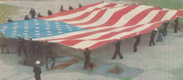 """Personnel at the Naval Reserve Center in Orange unfurl a giant flag Friday in preparation for today's Orange County Christmas parade. Retired Navy Chief Petty Officer Mike Jasper of Oklahoma City owns the flag, which measures 50 by 76 feet. About 40 Navy reservists will carry the flag in todays' parade."" File photo Dec. 10, 1988"