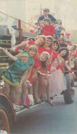 """Girls from Jazz Pizazz ride on the Beaumont Fire Department's antique ladder truck."" File photo Dec. 14, 1986"