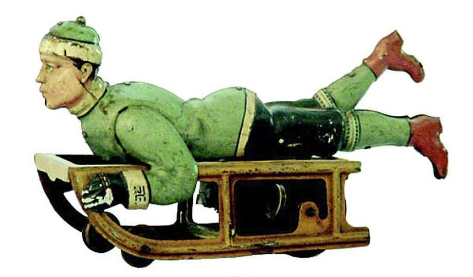 This lithographed tin boy-on-sled toy is 7 inches long. It sold at RSL Auction Co. for $334. Photo: Contributed Photo / The News-Times Contributed