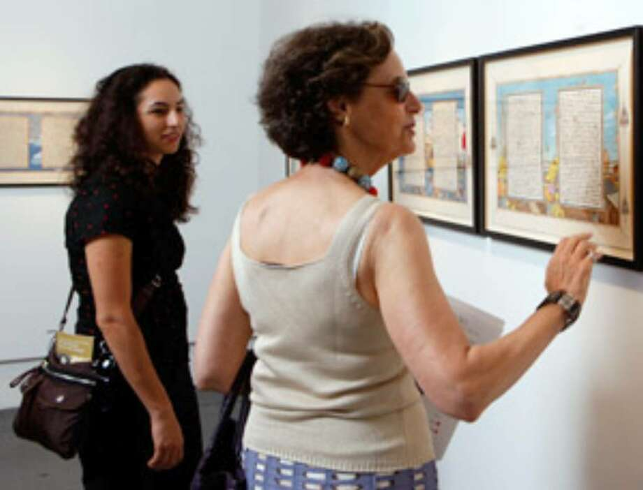 "Jennifer Schneiderman (left) and Barbara George look at the work of Sandow Birk, ""American Qur'an,"" at the Koplin Del Rio Gallery in Culver City, Calif."