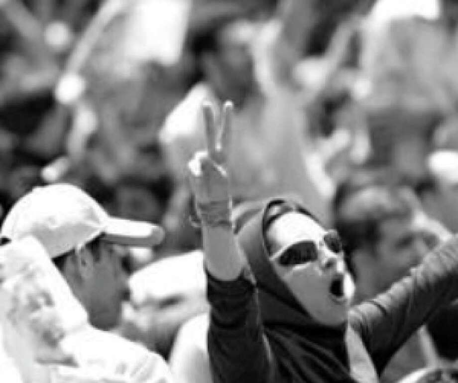 An Iranian opposition supporter flashes the victory sign  outside Tehran University in July. Iranian youth, from smaller families, seemingly have more of a sense of entitlement. And that spells trouble for the Iranian regime.