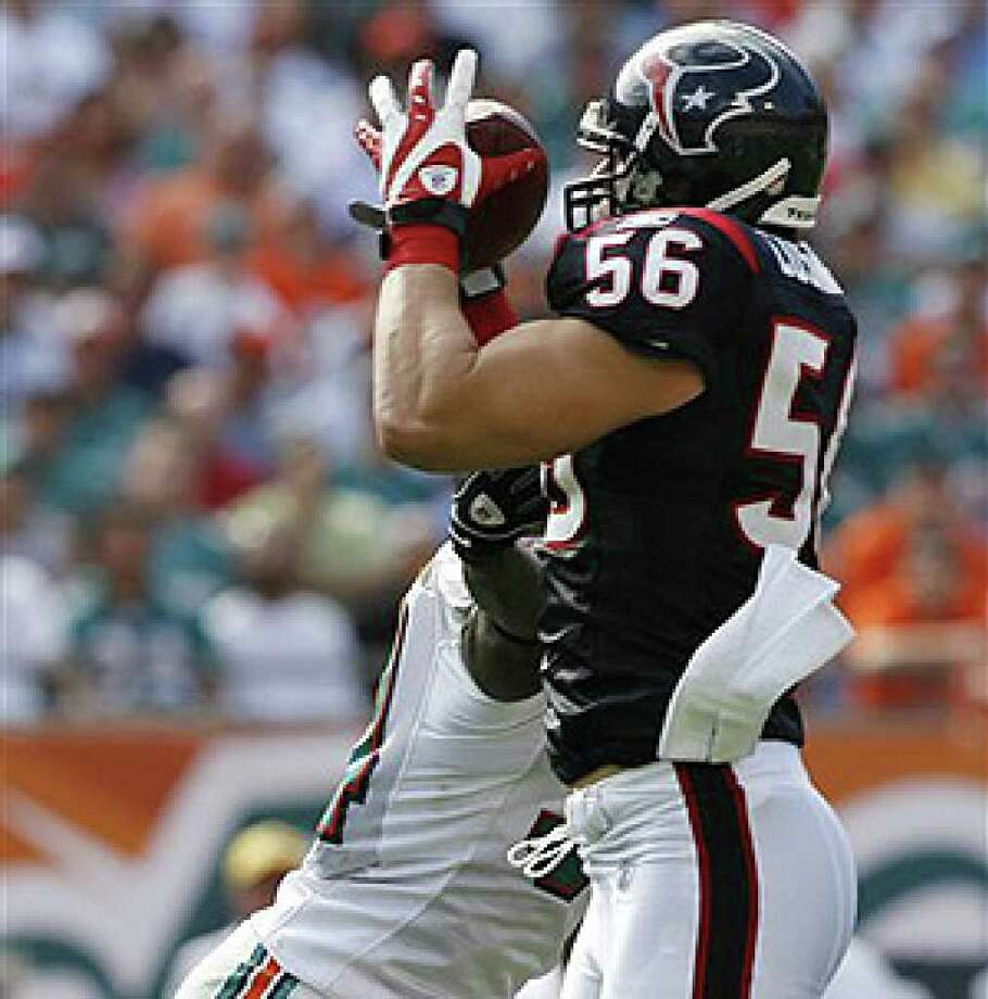 Texans linebacker Brian Cushing (right) intercepts a pass intended for Dolphins running back Ricky Williams (left).