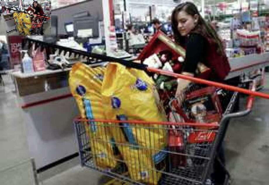 BJ's Wholesale Club checkout clerk Shelly LeRoy loads up a customer's purchases at a store in Camp Hill, Pa. Retail bright spots last month included Saks, Nordstrom, Costco, T.J. Maxx, Marshalls and Gap. But sales at most teen merchants were weak.