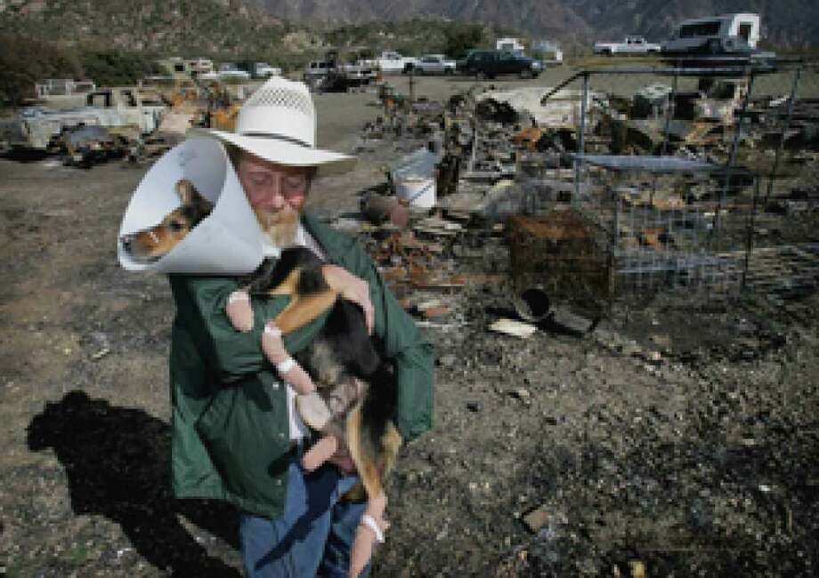 Bob Wright, 64, holds Lady, a Queensland heeler, whose paws were burned in the Sheep Fire, at his destroyed home in Lytle Creek, Calif.