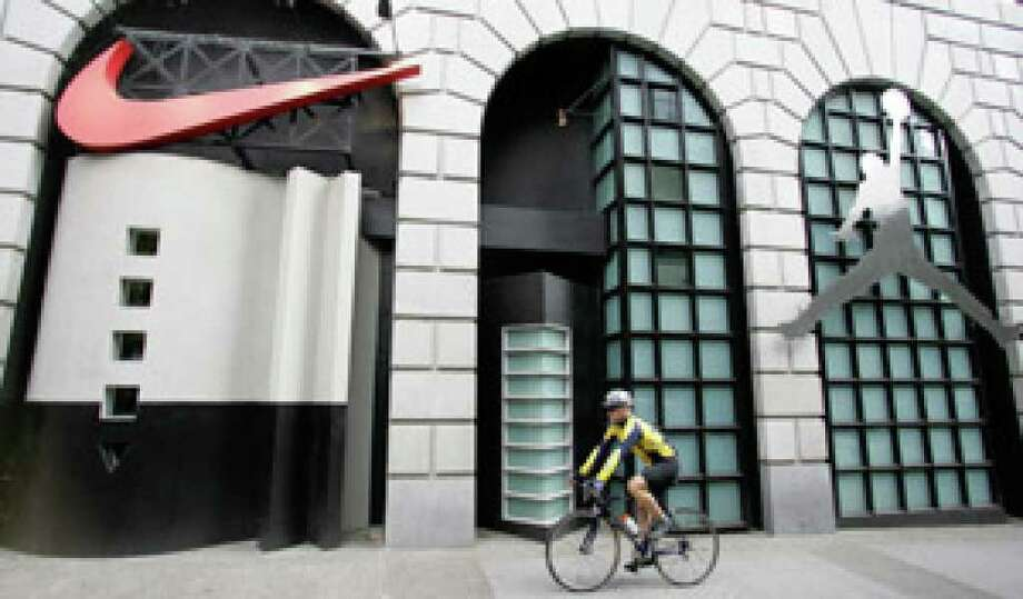 A cyclist rides past Niketown in Portland, Ore. For the second year in a row, Nike scored the highest in the Climate Counts survey at 83.