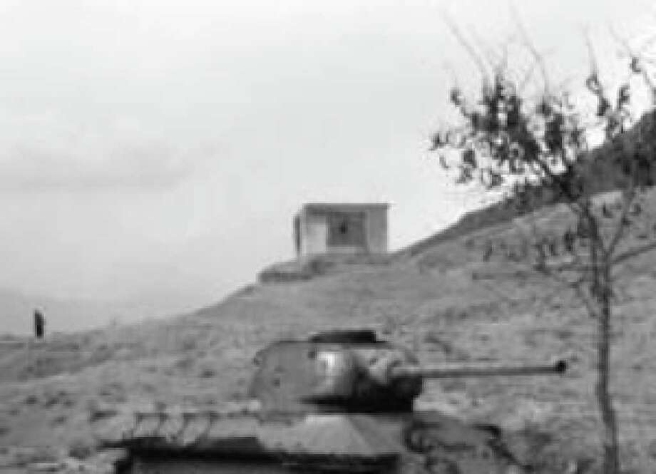"""A man rides a bicycle near an old destroyed Soviet tank, from the Russian-occupation era, south of Kabul, Afghanistan. The rugged and battle-worn country has been called """"the graveyard of empires."""""""