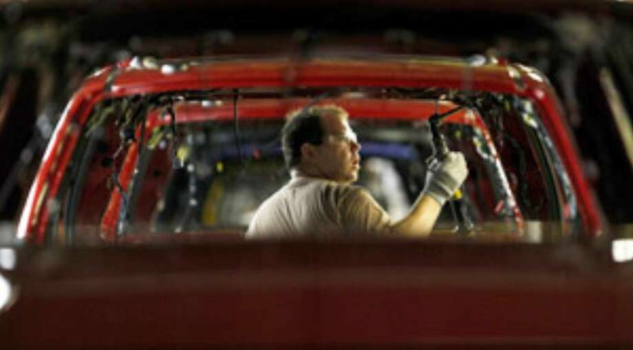Alex Stigall, of Richmond, Mo., attaches side airbags in a 2010 Ford Escape at Ford's assembly plant in Claycomo, Mo.