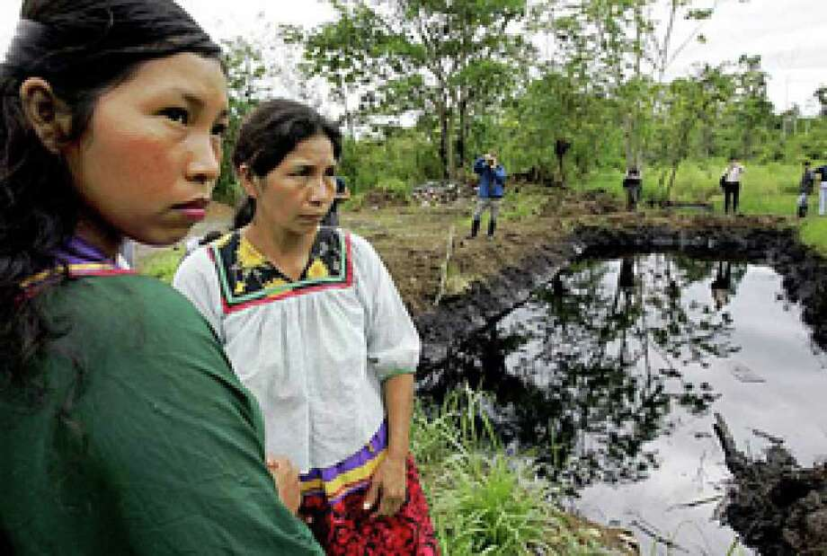 Ecuadoran women stand near a pool of oil in the country's rain forest where the soil and water have been polluted.
