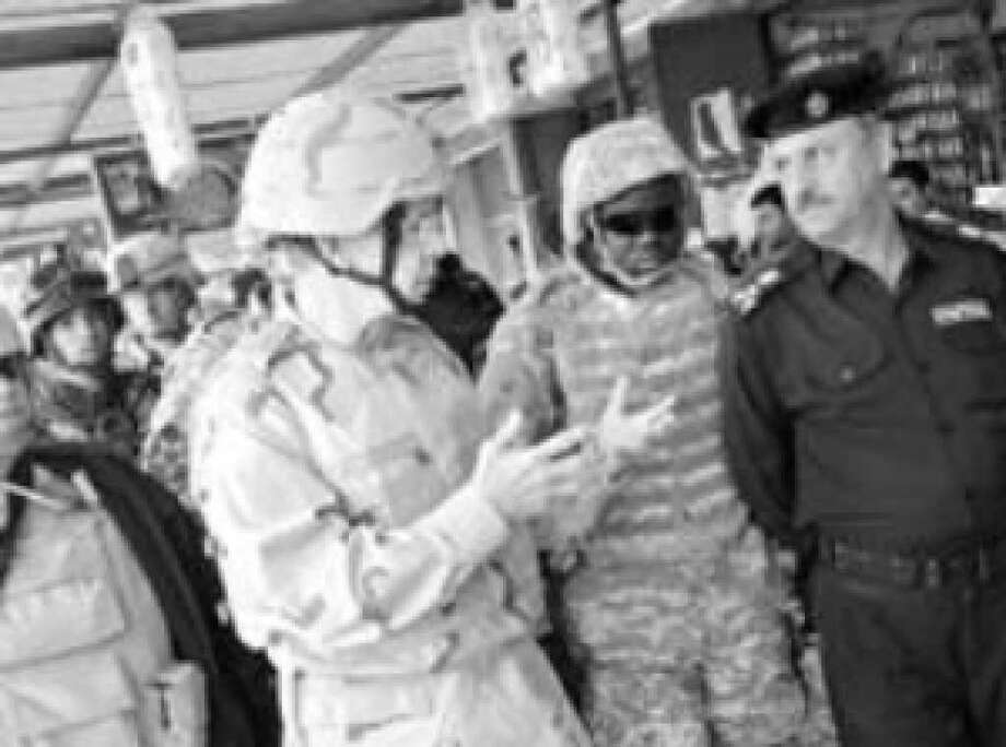 Adm. Mike Mullen, chairman of the Joint Chiefs of Staff (left), talks to Iraqi Brig. Gen. Nabeel Darwish Mohammad, police director for the town of Abu Ghraib, during a walk through the Abu Ghraib market.