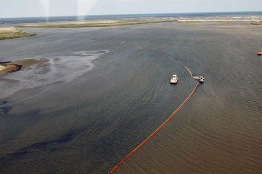 Workers place oil booms near the coast in Louisiana. Gov. Bobby Jindal said that least 10 wildlife areas are in the oil plume's path.