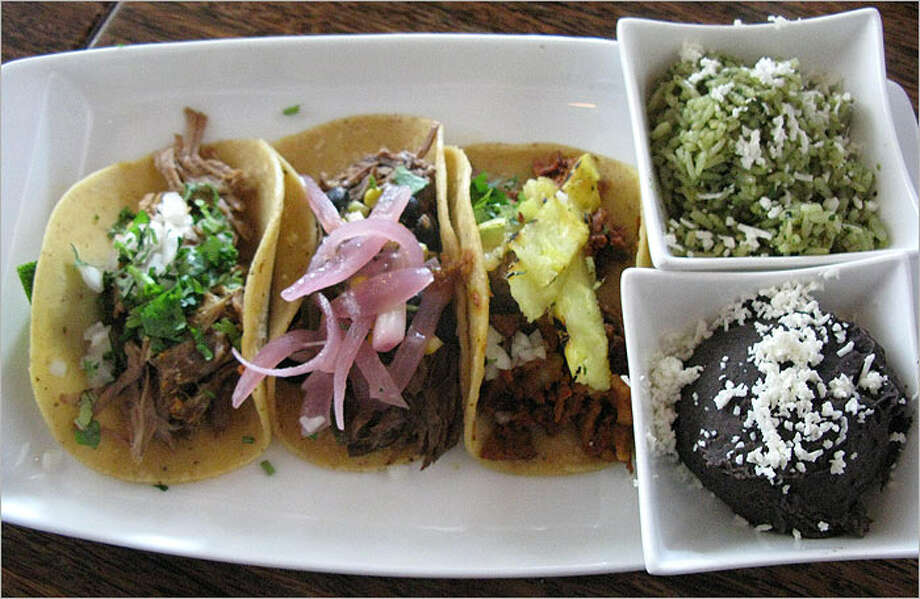 A three-taco plate is served with two side dishes for $9.75.