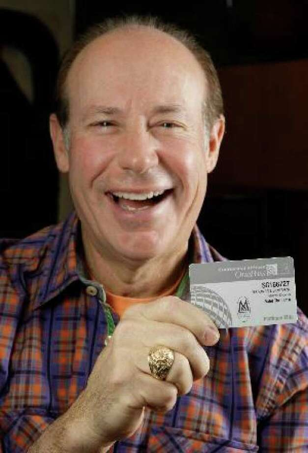 Rand Silverman holding his Million Miler Continental Airlines OnePass Platinum Elite card after bidding 1.75 million miles to visit the eight wonders of the world.