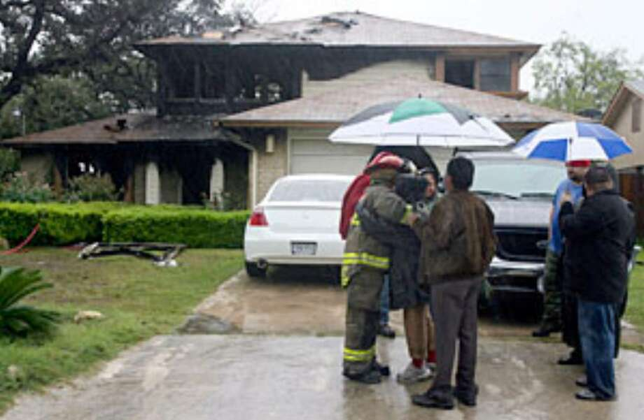A San Antonio firefighter hugs a woman after the home in the 8300 block of Exbourne Street went up in flames.