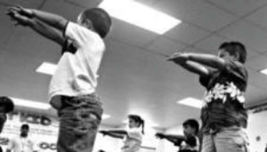 Children in Miami exercise during a Fit Kids session. Kids need daily exercise. But what encouragement can they expect from a generation of adults who have eliminated exercise even from opening a garage door?