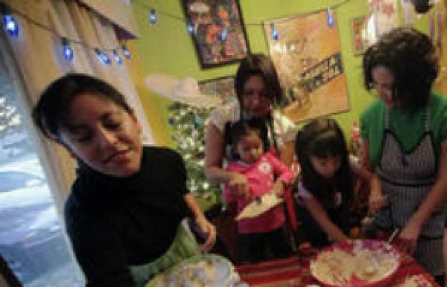 Mary Ponce (second from left) and Marisela Barrera (second from right) show their daughters Emma, 2, and Inez, 5, how to spread masa on a corn husk during their tamalada. Joining them were Anna De Luna (left) and Marisa Varela.
