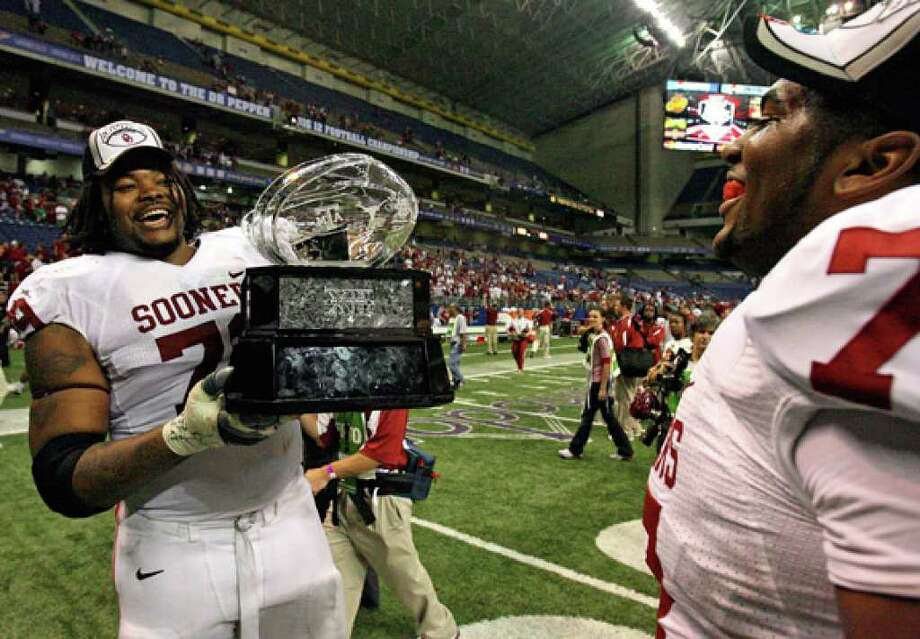 Oklahoma linemen Phil Loadholt (left) and Sherrone Moore celebrate with the Big 12 trophy after beating Missouri 38-17 on Dec. 1, 2007. The Big 12 championship was witnessed by 62,585 fans at the Alamodome.