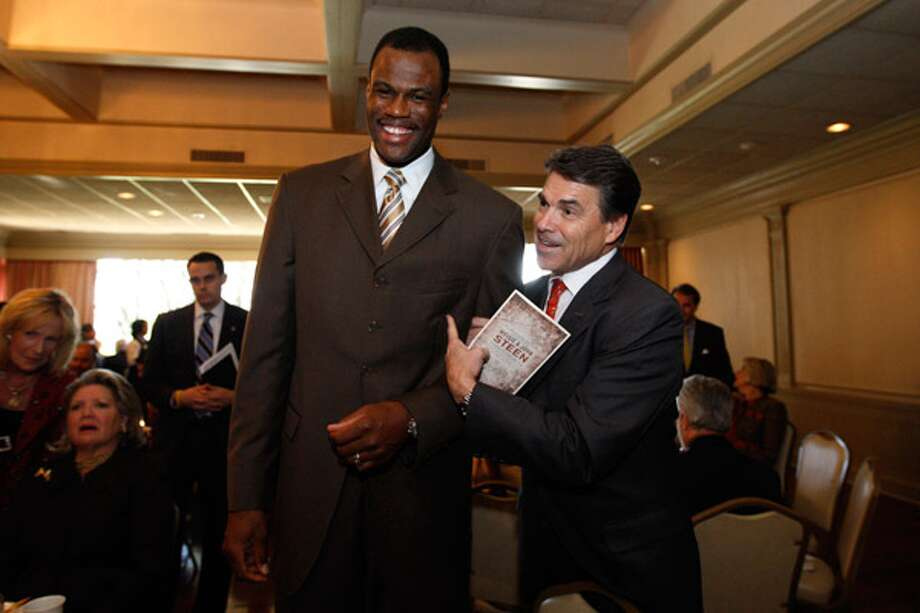 Rick Perry jokes with Spurs great David Robinson at the San Antonio Country Club before the governor speaks at a luncheon benefiting the Texas Association Against Sexual Assault.