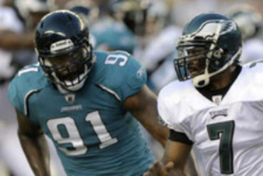 Eagles quarterback Michael Vick (right) scrambles past Jaguars defensive end Derrick Harvey in Philadelphia on Thursday night.