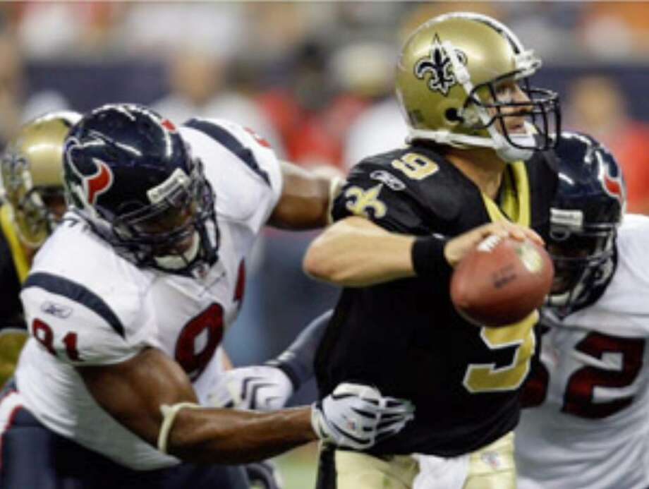 Texans defenders Amobi Okoye (left) and Xavier Adibi pressure Saints quarterback Drew Brees during the second quarter in Houston.