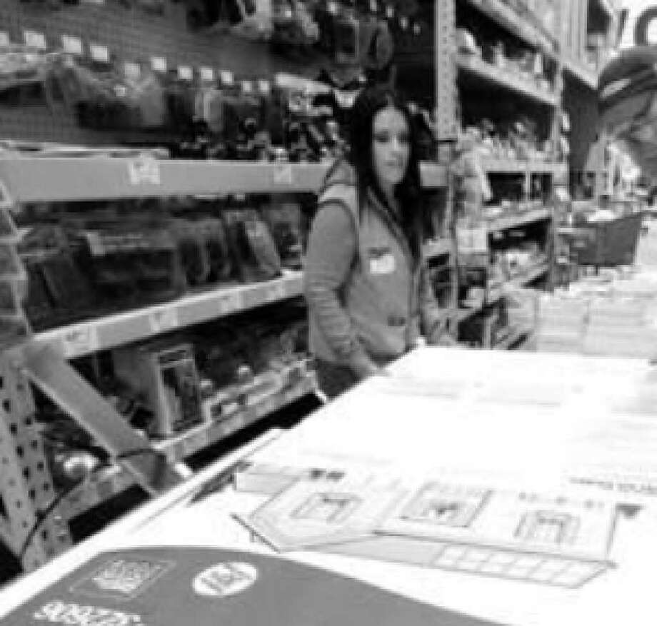 Lowe's associate manager Roxy Ramirez and associate Jim Miner stock do-it-yourself solar panels at a store in the West Hills suburb of Los Angeles.