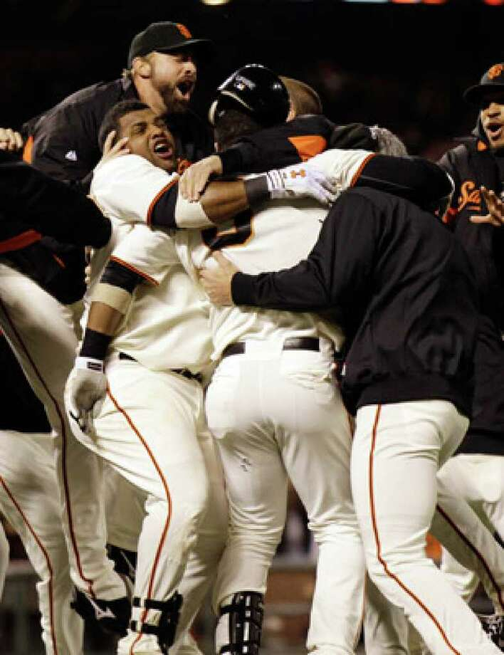 San Francisco's Juan Uribe (center) is swarmed by teammates after a game-winning sacrifice fly in the ninth inning.