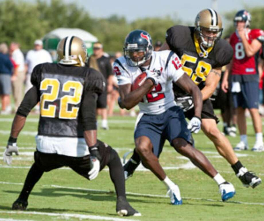 The Texans' Jacoby Jones (12), trying to elude Saints' defenders Tracy Porter (22) and Scott Shanle (58) during a joint practice this week, is trying to hold onto the No. 5 receiver spot.