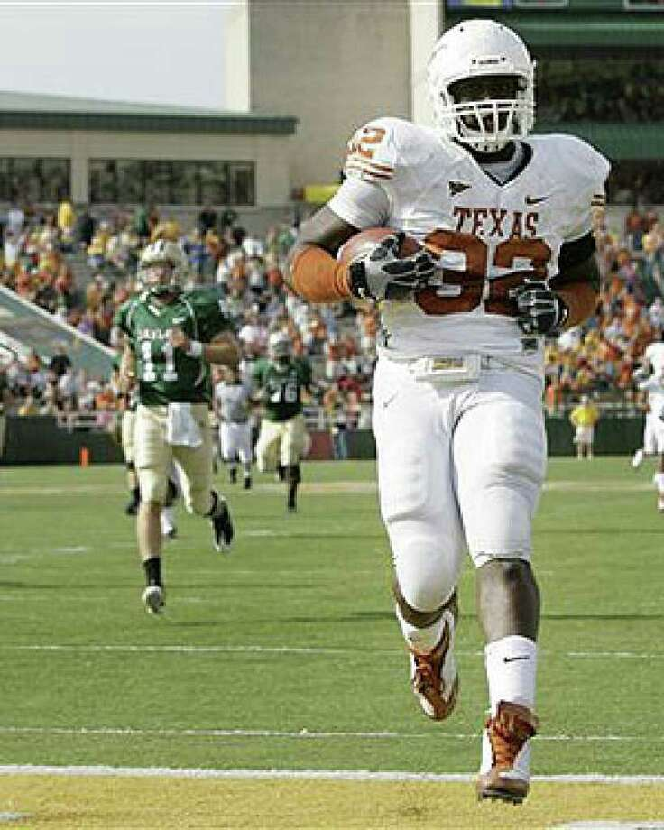 Texas defensive end Eddie Jones runs into the end zone for a touchdown after intercepting a pass from Baylor quarterback Nick Florence (left).