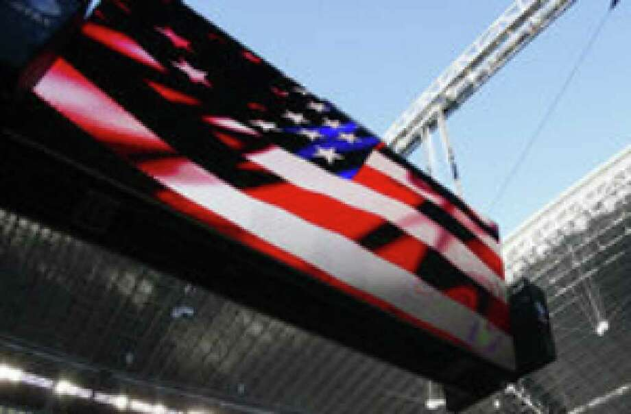 An American flag hangs in the end zone as a big one flies on the Jumbotron for 'America's Team' at Cowboys Stadium in Arlington.