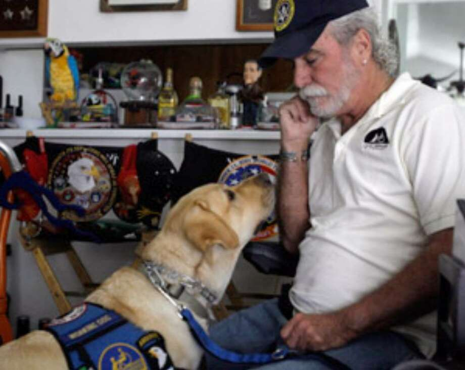 Vietnam veteran William Callahan, a paraplegic, teaches Taylor sign language at his home in Baytown. Having Taylor has enabled him to stay in his home, Callahan said.