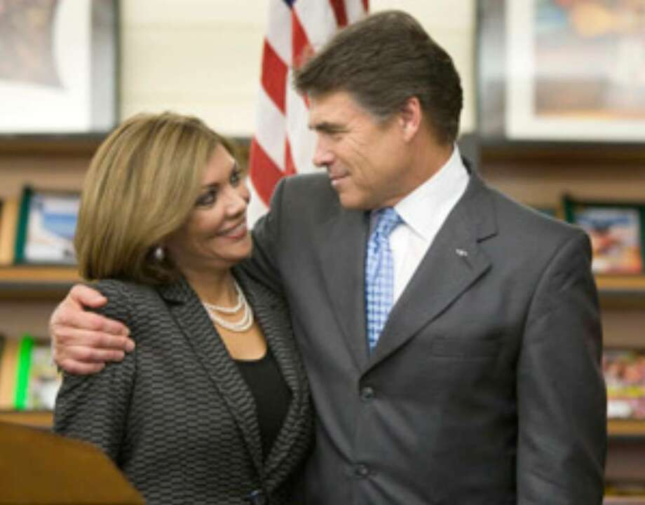 Justice Eva Guzman is embraced by Gov. Rick Perry after being appointed to replace Scott Brister on the Texas Supreme Court at a ceremony at Stephen F. Austin High School in Houston.