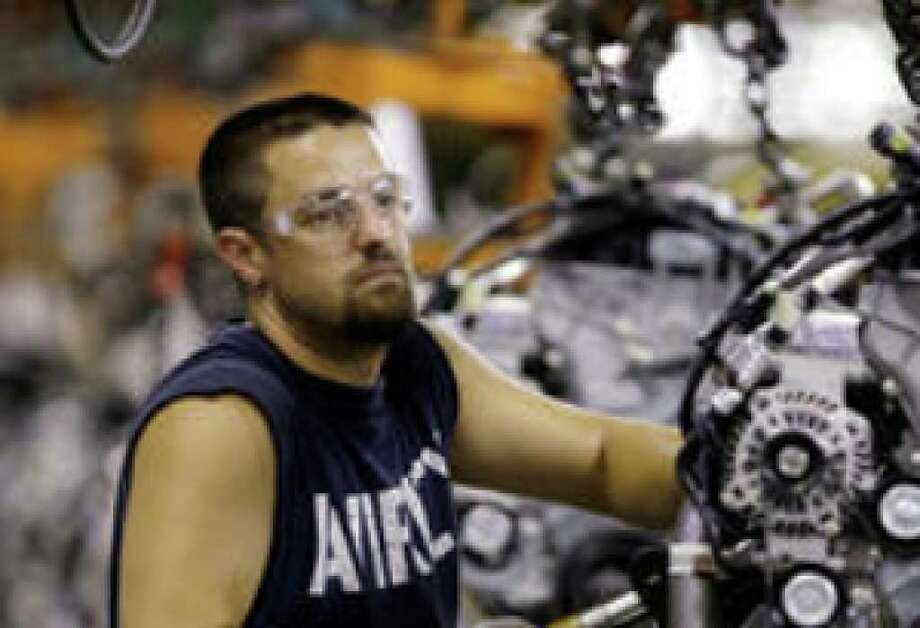An auto worker adjusts an engine for a 2010 Ford Escape. A private trade group said Tuesday that manufacturing activity grew for the fourth straight month in November.