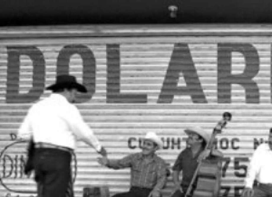 """Musicians in Monterrey, Mexico, mingle near sign that read """"dollars"""" in Spanish. If the economy is rough here, it's rougher in Mexico."""