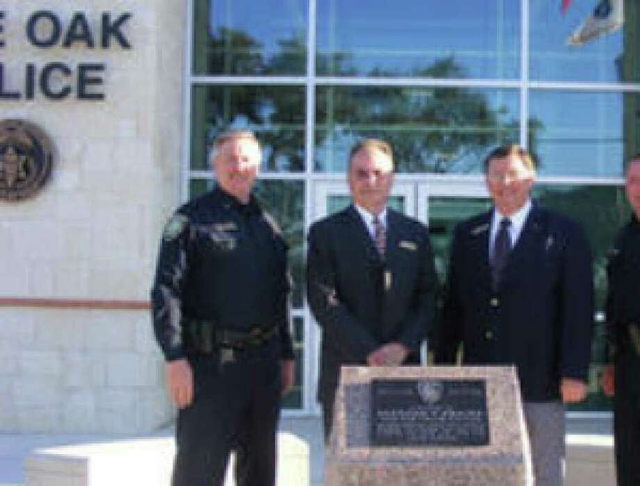 Standing outside the new Live Oak Justice Center are (from left), Dan Pue, assistant police chief; Matt Smith, city manager; Joe Painter, mayor; and Ron Echols, police chief. The granite marker is a dedication to officer Alfredo Araiza, who died in the line of duty.