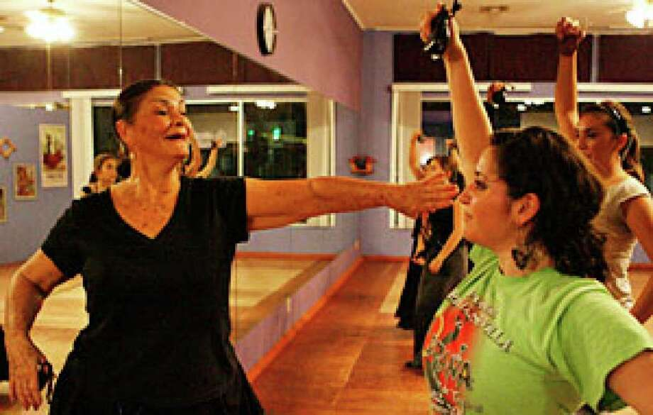 Chiqui Linares watches over Crystal Caballero as she practices her dance moves.