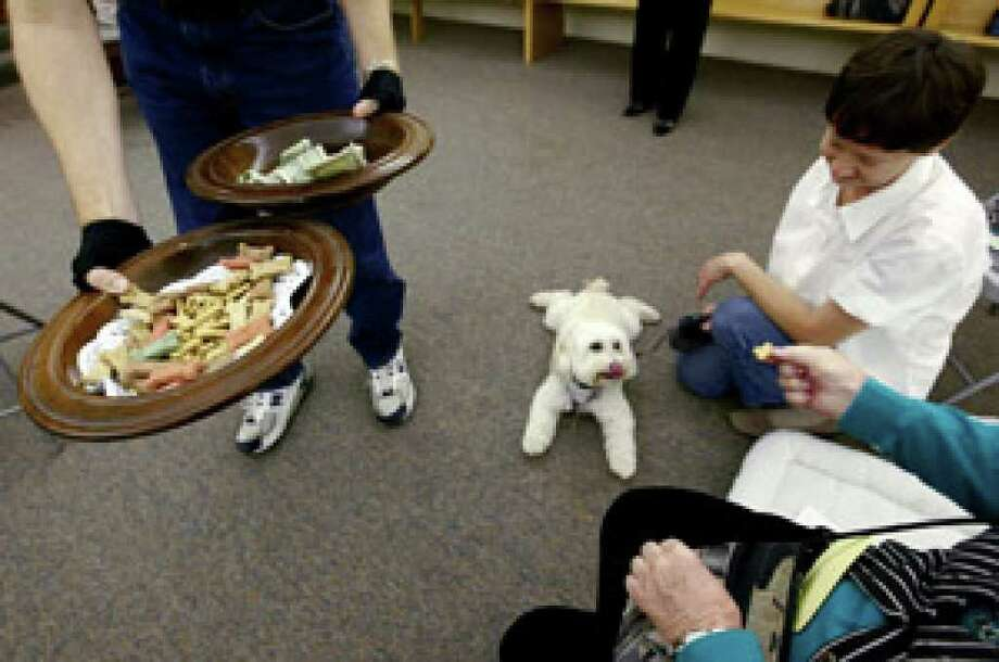 The collection plate and a plate of dog treats make the rounds after services at Covenant Presbyterian Church.