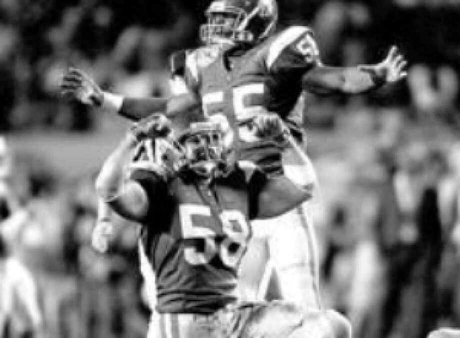 Southern Cal's Lofa Tatupu (58) and Keith Rivers (55) react after Tatupu sacked Oklahoma's Jason White during the 2005 Orange Bowl at Miami's Pro Player Stadium.