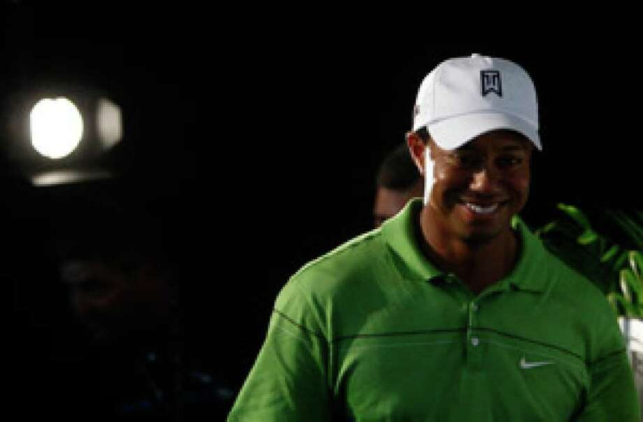 A spotlight shines on Tiger Woods as he leaves a press conference Tuesday in Melbourne, Australia. Woods will play in the Australia Masters, and the tournament is already sold out.